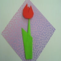 An origami tulip with a red flower and green stem