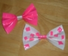 Two duct tape hair bows, one made from pink tape, and the other made from white tape with pink polka dots