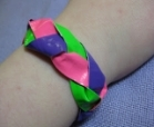 A bracelet made from strips of colorful duct tape braided together