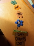 A flower pot shaped card with flowers coming out of it on a string