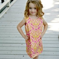 Young girl in a pink and yellow patterned shift dress