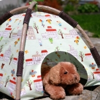 A miniature camp-style tent with a stuffed dog inside