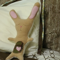 A sewn, stuffed bunny on a pillow