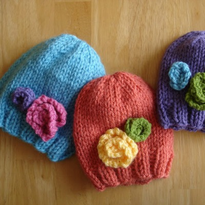 Blue, red, and purple knitted baby hats with flowers on them