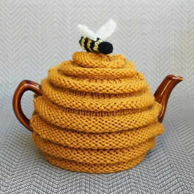 Purple knitted tea cozies on teapots