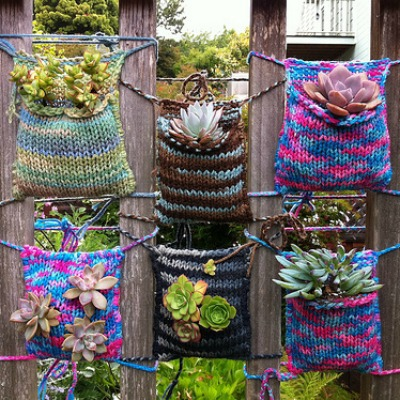 A knitted pocket attached to a fence and containing a flower