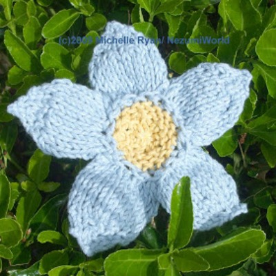 A knitted blue flower among green grass and leaves