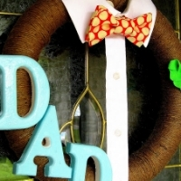 "A brown wreath with a collar and bowtie, and the word ""Dad"""