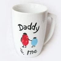 "A white mug with two thumbprint people and the words ""Daddy and me"""