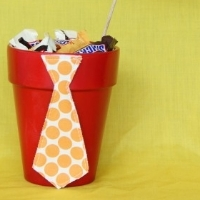 "A small, painted flower pot filled with candy and a ""Happy Father"