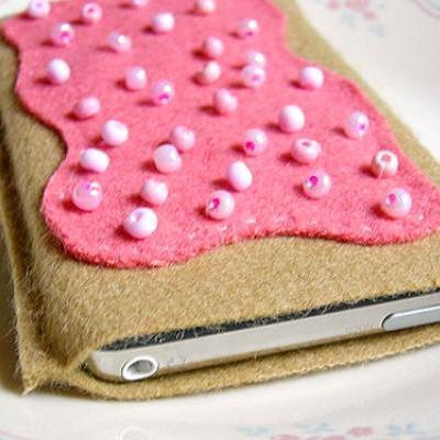 An iPod cozy made of brown felt with pink faux frosting and sprinkles on top
