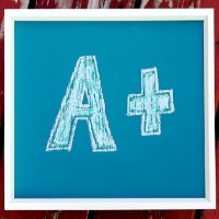 "A wooden panel painted with chalkboard paint with an ""A+"" written on it"