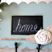 "A frame whose inner rectangle is painted with chalkboard paint and has the word ""home"" written on it"