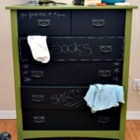 A dresser whose drawers are painted with chalkboard paint