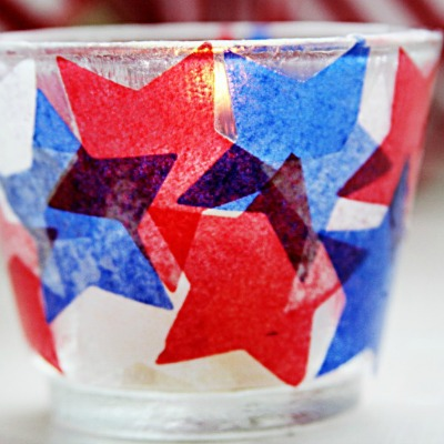 A glass candle holder covered in tissue paper stars