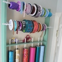 Ribbon and wrapping paper organized on wooden dowels