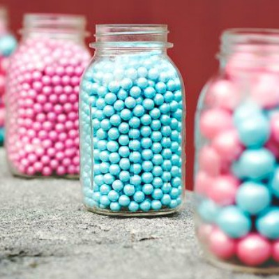 Jars filled with pink and blue gumballs for gender reveal party