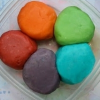 Five balls of homemade play dough in red, purple, green, blue, and orange