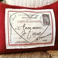 A red pillow with a valentine telegram written in French stitched to the front
