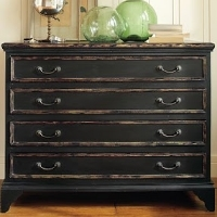 A dresser with a vintage, worn black paint finish
