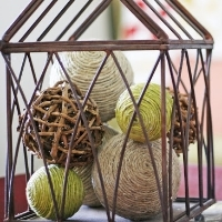 Several decorative balls made of twine in a bronze bird cage