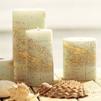 Three cylindrical candles, all covered in map-patterned scrapbook paper