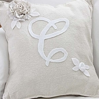 A pillow with a large letter C stitched on the front