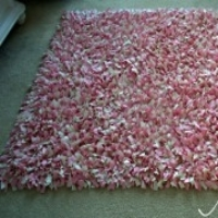 Pink and white fabric tied together to create a shag rug effect