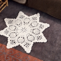 A bedroom with a white crocheted rug that looks like a doily on the carpet
