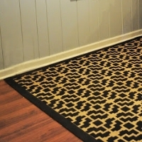 A black and beige rug with a geometric pattern stenciled on it