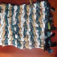 A rug made from plastic bags and black garbage bags woven together
