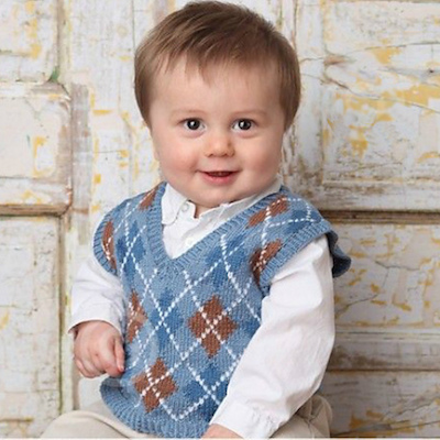 A toddler boy in a blue sweater vest with white and brown detail on the front