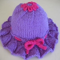 A purple hat with a ruffled brim and a pink ribbon around the brim