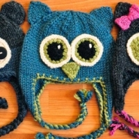 Three hats in the shape of owl heads with ear flaps and eyes