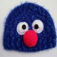 A blue hat with a red nose and eyes that looks like Grover from Sesame Street