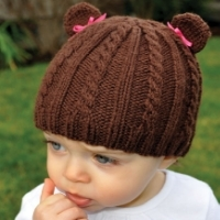 A brown, cabled hat with ears on top to make it look like a teddy bear