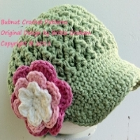 A newsboy style hat in green with a pink flower on the side