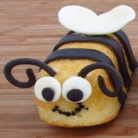 A Twinkie decorated with black candy strips and candy eyes to look like a bee