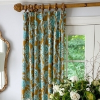 Blue and brown patterned curtains hanging in front of a window