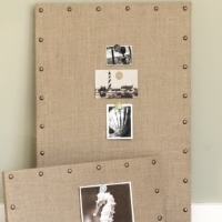 Two cork boards covered in burlap with upholstery nails around the edges
