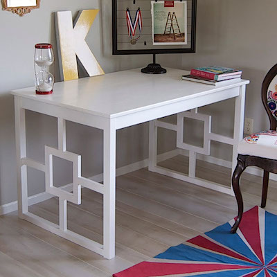 A wooden table painted white, with a design inset into each side