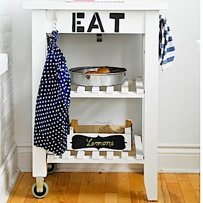 "A kitchen cart painted white with the word ""EAT"" stenciled on the side"