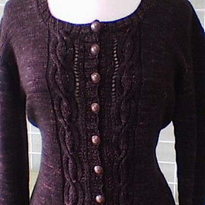 A thick purple cardigan with buttons down the front and a cabled pattern
