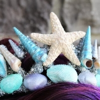 A plastic tiara covered with painted seashells and a starfish