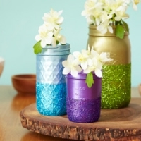 Three mason jars, each painted a different color and covered in glitter