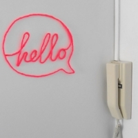 "A word bubble with the word ""hello"" made from craft wire hanging on the wall"