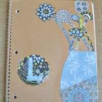 A cardboard notebook cover decorated with scrapbook paper in different shapes