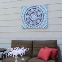A patio with wall art made from a shower curtain hanging on the house