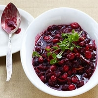 Cranberry sauce in a white bowl with a spoon next to it