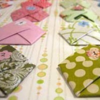 Six small origami envelopes mounted on cardstock